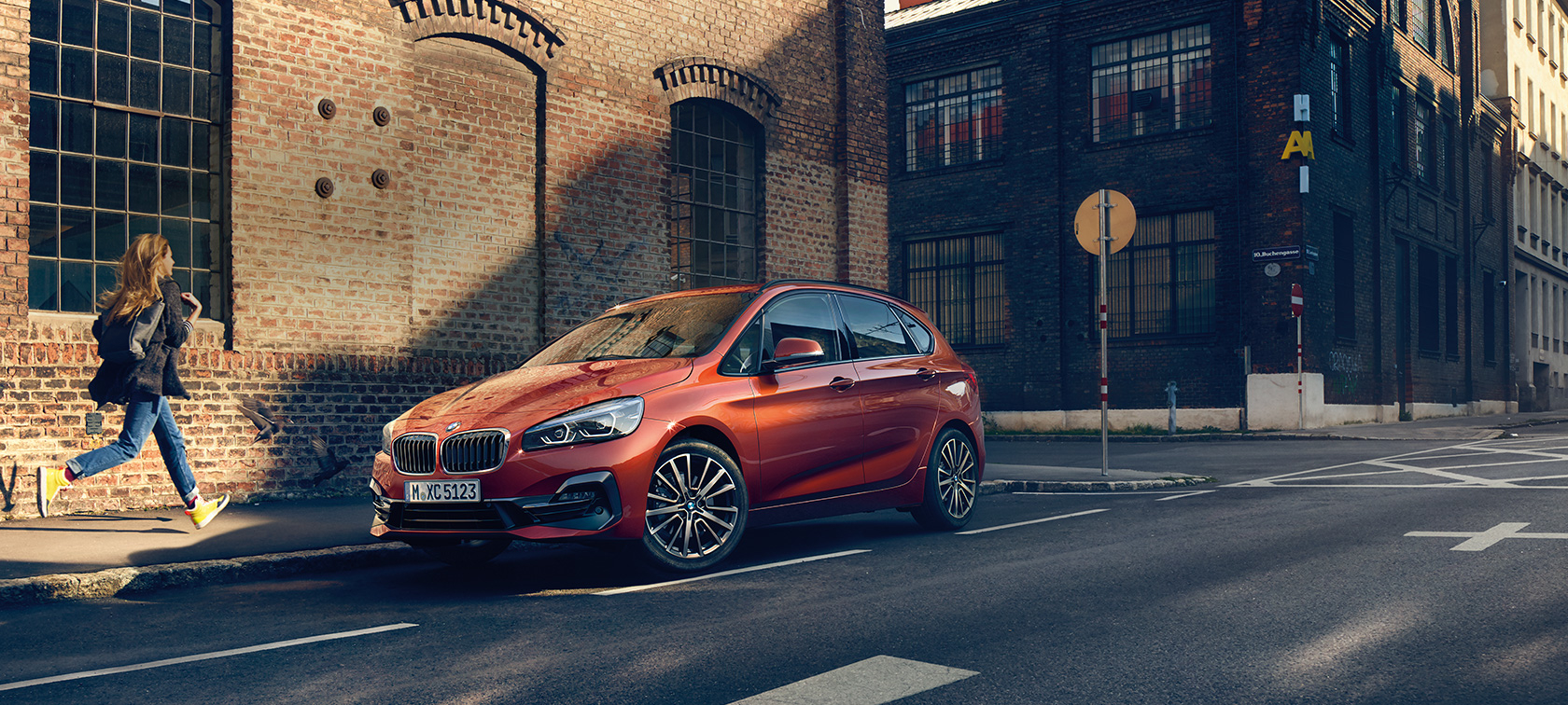 BMW 2-serie Active Tourer F45 Facelift 2018 Sunset Orange metallic sedd snett framifrån parkerad på gatan